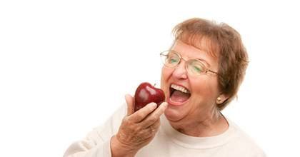 Woman with a dental implant biting an apple.