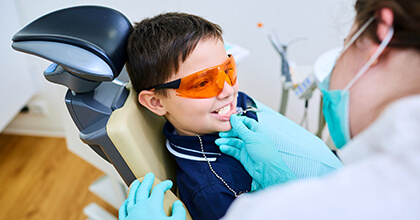 Young boy with protective glasses receives dental sealants