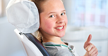 Young girl in dental chair gives thumbs up