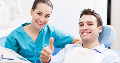 Man in dental chair giving thumbs up