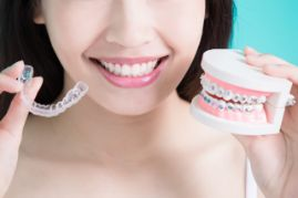 Woman holding braces in one hand and Invisalign in another