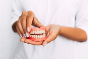 Woman holding a broken denture that has been repaired